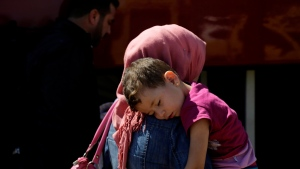 A woman with her child migrant from Syria walk towards a refugee camp at Kokkinotrimithia, outside of the capital Nicosia, in the eastern Mediterranean island of Cyprus, on Sunday, Sept. 10, 2017. Cyprus police say a 36-year-old man has been arrested for allegedly driving one of a pair of boats that brought 305 Syrian refugees to the island's northwestern coast. (AP Photo/Petros Karadjias)