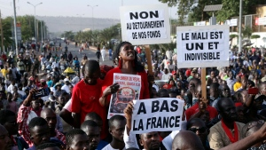 "In this photo taken on Friday, Nov. 15, 2019, people hold signs reading in French ""down with France"" ""Mali is one and indivisible' and ""no to the misappropriation of our funds"" during a protest against France but showing support to the Malian army and the families of Malian soldiers who died during the fight against terrorism, at the Independence square in Bamako, Mali. Mali's military has abandoned some of its most isolated outposts in the desert north while extremist attacks have killed more than 100 soldiers in just six weeks. The West African nation's president faces a decline in military morale, a sentiment that helped spark a coup against his predecessor in 2012. (AP Photo/Baba Ahmed)"