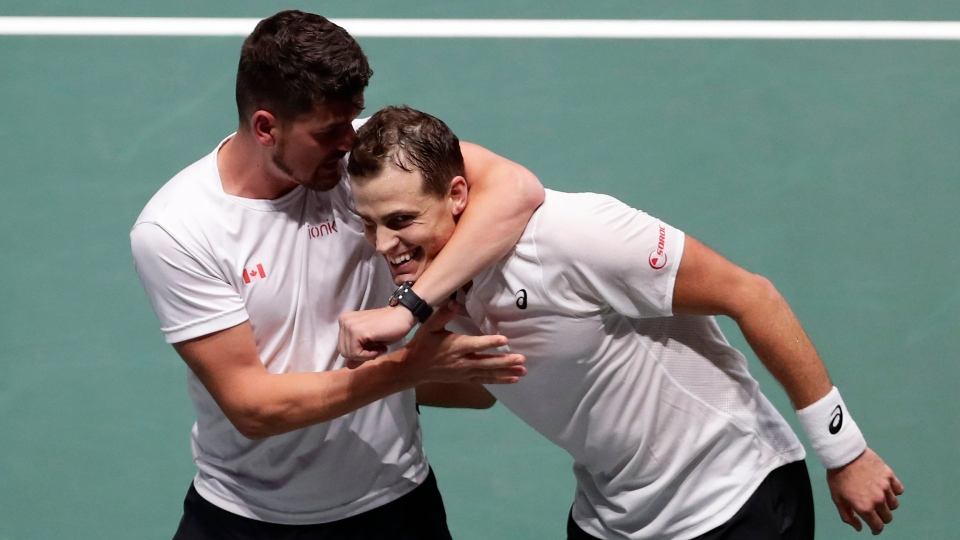 Canada's Vasek Pospisil, right, celebrates his victory with Canada's captain Frank Dancevic after his victory over Australia's John Millman during the Davis Cup tennis match in Madrid, Spain, Thursday, Nov. 21, 2019. (AP Photo/Manu Fernandez)
