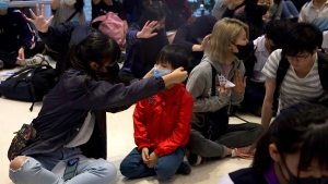 """A woman puts a mask on a boy's face during a sit-in at a shopping mall to commemorate the four-month anniversary of an assault on commuters and protesters by armed men at a nearby train station in Hong Kong, Thursday, Nov. 21, 2019. A small but determined group of protesters remained holed up Thursday inside a Hong Kong university campus as the city's largest pro-Beijing political party urged voters to """"kick out the black force"""" in upcoming elections seen as a key gauge of public support for anti-government protests. (AP Photo/Ng Han Guan)"""