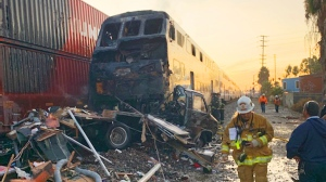 This photo provided by the Norwalk Sheriff's Station shows first responders at the scene after an RV was hit by a commuter train and burst into flames along a track in Santa Fe Springs, Calif., Friday, Nov. 22, 2019.  (Norwalk Sheriff's Station via AP)