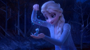 "This image released by Disney shows Elsa, voiced by Idina Menzel, sprinkling snowflakes on a salamander named Bruni in a scene from the animated film, ""Frozen 2."" (Disney via AP)"