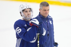 Newly appointed head coach Toronto Maple Leafs Sheldon Keefe, right, stands alongside Alexander Kerfoot, as runs a practice session in Toronto on Monday, November 25, 2019. THE CANADIAN PRESS/Chris Young