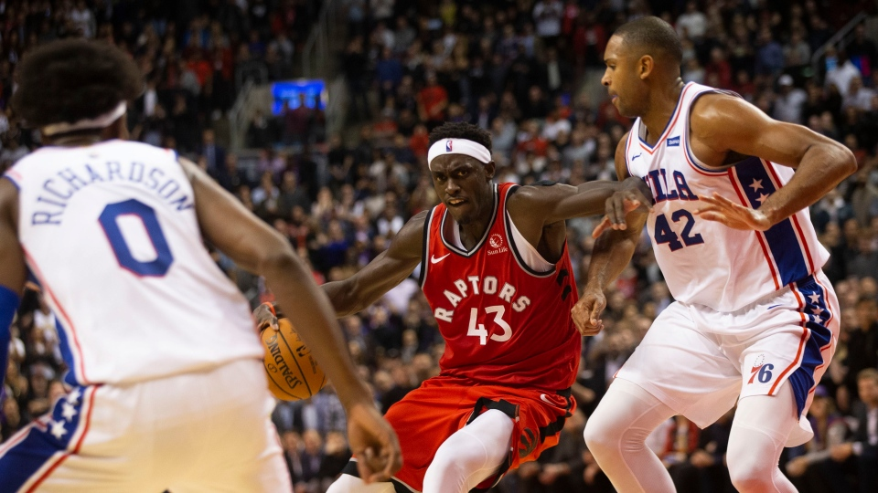 Toronto Raptors forward Pascal Siakam protects the ball from Philadelphia 76ers' Al Horford during second half NBA basketball action in Toronto on Monday, November 25, 2019. THE CANADIAN PRESS/Chris Young