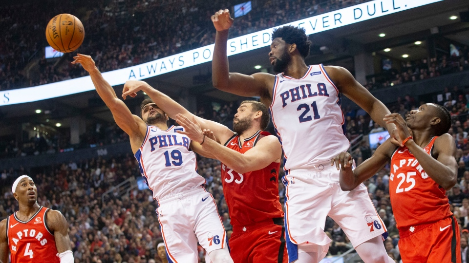 Philadelphia 76ers guard Raul Neto (19) jumps for a rebound ahead of Toronto Raptors' Marc Gasol (33) as 76ers' Joel Embiid (21) and Raptors' Chris Boucher (25) and Raptors' Rondae Hollis-Jefferson (4) look on during first half NBA basketball action in Toronto on Monday, November 25, 2019. THE CANADIAN PRESS/Chris Young
