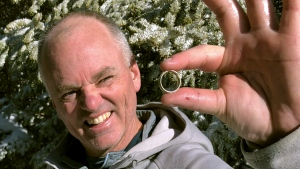In this Nov. 13, 2019, photo provided by Brendan Cheever, Tom Gately displays a gold wedding band he found by using a metal detector on snow covered on Mount Hancock New Hampshire's White Mountains. Bill Giguere, of North Andover, Mass., had been wearing the ring for three years and put out a plea to a hiking group for help after he lost it while hiking the previous week. (Brendan Cheever via AP)