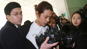 FILE - In this March 14, 2019, file photo, K-pop singer Jung Joon-young, center, arrives at the Seoul Metropolitan Police Agency in Seoul, South Korea. (AP Photo/Ahn Young-joon, File)