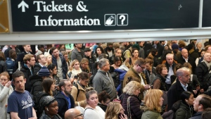 Travelers wait to board their trains at Penn Station in New York, Wednesday, Nov. 27, 2019. A day after bringing havoc to the Rocky Mountains, a powerful winter storm rolled across the Midwest on Wednesday, threatening to scramble Thanksgiving plans for millions of people during one of the busiest travel weeks of the year.(AP Photo/Seth Wenig)