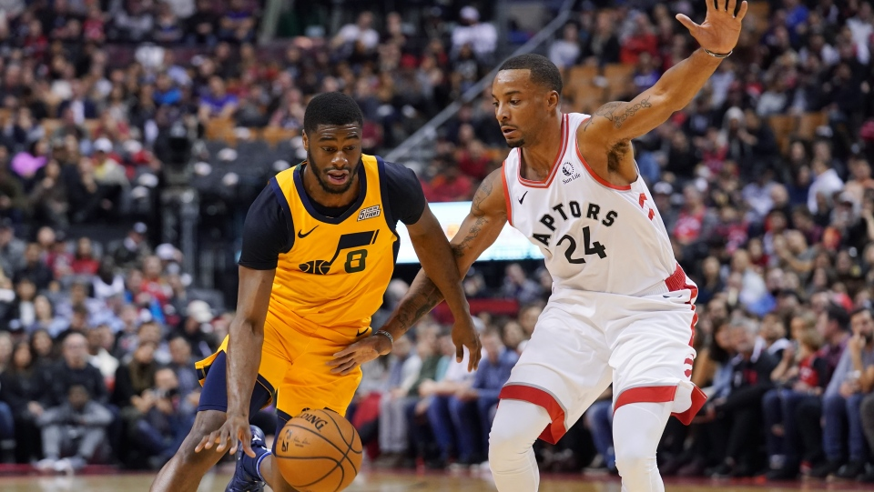 Utah Jazz's Emmanuel Mudiay (8) drives to the basket as Toronto Raptors' Norman Powell (24) defends during first half NBA basketball action in Toronto, Sunday, Dec. 1, 2019. THE CANADIAN PRESS/Hans Deryk
