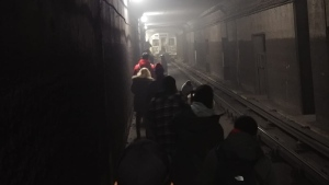 TTC passengers walk down a subway tunnel as they are evacuated from a train on Line 2. (Photo submitted by Tyler Patterson)