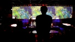 A man stands in the rows during the final of League of Legends tournament between Team G2 Esports and Team FunPlus Phoenix, in Paris, Sunday, Nov. 10, 2019. (AP Photo/Thibault Camus)