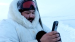 Puasi Ippak tests out the Siku mobile app in a handout photo. A social media app geared towards the outdoor lives of Inuit launched Wednesday with features that tie traditional knowledge to smart phone technology. THE CANADIAN PRESS/HO-Arctic Eider Society MANDATORY CREDIT