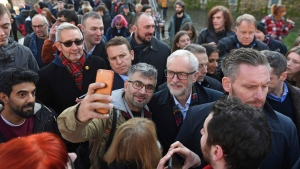 Britain's main opposition Labour Party leader Jeremy Corbyn, centre right, has a selfie photo taken with supporters, while on the General Election campaign trail in Nottingham, England, Wednesday Dec. 4, 2019. Britain's Brexit is one of the main issues for political parties and for voters, as the UK goes to the polls in a General Election on Dec. 12. (Joe Giddens/PA via AP)