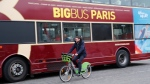 A man rides a bicycle next to a tourists bus in Paris, Thursday, Dec. 5, 2019. The Eiffel Tower shut down Thursday, France's vaunted high-speed trains stood still and teachers walked off the job as unions launched nationwide strikes and protests over the government's plan to overhaul the retirement system. (AP Photo/Francois Mori)