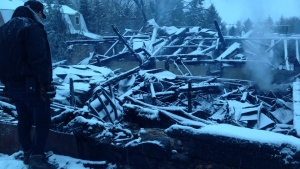 Brooks Farm owner Paul Brooks surveys the damage after a massive fire at a barn on the farms grounds. (Cam Woolley)