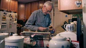 In this Nov. 22, 2019, photo, Charles Flagg, who has Alzheimer's disease, makes a peanut butter sandwich for lunch at his family home in Jamestown, R.I. (AP Photo/Charles Krupa)
