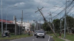 Vehicles pass by toppled electrical poles as Typhoon Kammuri slammed Legazpi city, Albay province, southeast of Manila, Philippines on Tuesday, Dec. 3, 2019. (AP Photo)
