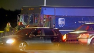 Law enforcement stand near a vehicle that appears to be part of the crime scene where four people were killed, Thursday, Dec. 5, 2019 in Miramar, Fla. The FBI says four people, including a UPS driver, were killed after robbers stole the driver's truck and led police on a chase that ended in gunfire at a busy Florida intersection during rush hour. (Charles Trainor Jr./Miami Herald via AP)