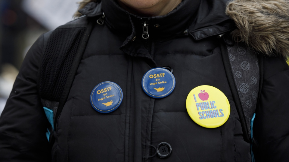A striking teacher of the Ontario Secondary School Teachers' Federation pickets outside of the Toronto District School Board head office on Yonge St. in Toronto, Wednesday, Dec. 4, 2019. The union representing Ontario's public high school teachers says it will hold another one-day strike on Dec. 11. THE CANADIAN PRESS/Cole Burston