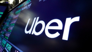 In this Friday, Aug. 16, 2019 file photo, the logo for Uber appears above a trading post on the floor of the New York Stock Exchange. (AP Photo/Richard Drew, file)