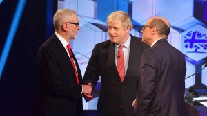 Opposition Labour Party leader Jeremy Corbyn, left, shakes hands with Britain's Prime Minister Boris Johnson, centre, with debate moderator TV presenter Nick Robinson, right, during a head to head live Election Debate at the BBC TV studios in Maidstone, England, Friday Dec. 6, 2019. Britain's Brexit is one of the main issues for political parties and for voters, as the UK prepares for a General Election on Dec. 12. ( Jeff Overs/BBC via AP)