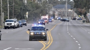 Police cars escort an ambulance after a shooter open fire inside the Pensacola Air Base, Friday, Dec. 6, 2019 in Pensacola, Fla. The US Navy is confirming that a shooter is dead and several injured after gunfire at the Naval Air Station in Pensacola. (Tony Giberson/ Pensacola News Journal via AP)