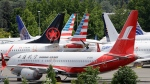FILE - In this Thursday, June 27, 2019 file photo, dozens of grounded Boeing 737 MAX airplanes crowd a parking area adjacent to Boeing Field in Seattle. (AP Photo/Elaine Thompson, File)