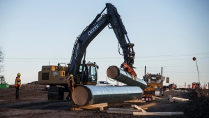 Workers unload pipe to start of right-of-way construction for the Trans Mountain Expansion Project, in Acheson, Alta., Tuesday, Dec. 3, 2019. THE CANADIAN PRESS/Jason Franson