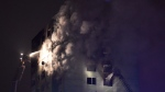 Smoke billows as emergency services work into the night at the scene of an explosion, and subsequent fire at an apartment building in Presov, Slovakia, on Friday Dec. 6, 2019. The explosion occurred toward the top of the 12-storey building and a spokeswoman for the rescue services said more than 40 people were injured. (Frantisek Ivan/TASR via AP)