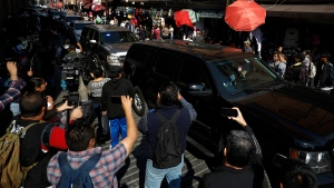 Journalists film as the convoy carrying U.S. Attorney General William Barr departs from the National Palace, where Barr met privately with President Andres Manuel Lopez Obrador and Foreign Minister Marcelo Ebrard, in Mexico City, Thursday, Dec. 5, 2019. Barr's closed-door meetings in Mexico come about one week after President Donald Trump suggested that the United States would seek to classify Mexican drug cartels as terrorist organizations. (AP Photo/Rebecca Blackwell)