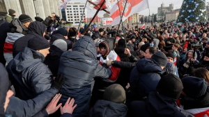 Protesters argue with pro-government people dressed in black, foreground, during a rally in downtown Minsk, Belarus, Saturday, Dec. 7, 2019. Several hundreds demonstrators gathered to protest against closer integration with Russia. (AP Photo/Sergei Grits)