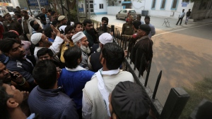 Mehaboob Alam, center with white beard, waits outside a mortuary to identify and collect the bodies of two nephews who died in a fire in New Delhi, India, Sunday, Dec. 8, 2019. Dozens of people died on Sunday in a devastating fire at a building in a crowded grains market area in central New Delhi, police said. (AP Photo/Manish Swarup)