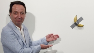 "In this Dec. 4, 2019 photo, gallery owner Emmanuel Perrotin poses next to Maurizio Cattlelan's ""Comedian"" at the Art Basel exhibition in Miami Beach, Fla. The work sold for $120,000. (AP Photo/Siobhan Morrissey)"
