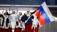 FILE - In this Feb. 7, 2014 file photo Alexander Zubkov of Russia carries the national flag as he leads the team during the opening ceremony of the 2014 Winter Olympics in Sochi, Russia.  (AP Photo/Mark Humphrey, file)
