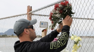 A man places a bouquet to a fence on the waterfront in Whakatane, New Zealand, Tuesday, Dec. 10, 2019. Unstable conditions hampered rescue workers from searching for at least eight people missing and feared dead after a volcano off the New Zealand coast erupted on Monday Dec 9 in a towering blast of ash and scalding steam while dozens of tourists explored its moon-like surface. Five deaths have been confirmed. (AP Photo/Mark Baker)