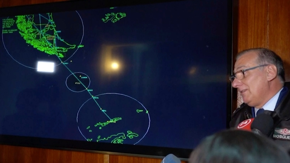 In this image made from video, Gen. Eduardo Mosqueira, right, of the Fourth Air Brigade speaks to the media next to a map of the area where the airplane is missing, in Punta Arenas, Chile, Monday, Dec. 9, 2019. Chile's air force lost radio contact with a transport plane carrying 38 people on a flight Monday evening to the country's base in Antarctica, and authorities indicated several hours later that they were not optimistic about the aircraft's fate. The military said earlier that it had declared an alert and activated search and rescue teams. (AP Photo)