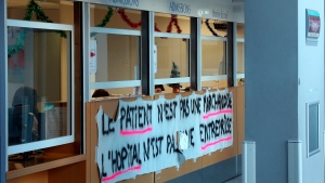 "A banner that reads: ""The patient is not a commodity, the hospital is not a business"" is displayed in the hospital of Bayonne, Tuesday Dec. 10, 2019. French airport workers, teachers and others joined nationwide strikes Tuesday as unions cranked up pressure on the government to scrap changes to the national retirement system. (AP Photo/Bob Edme)"