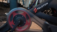 The Peloton logo is displayed on the company's stationary bicycle, Thursday, Sept. 26, 2019 in New York. A controversial ad for an expensive stationary bike is unlikely to damper the exercise-equipment retailer's holiday sales, experts say, but may actually boost them thanks to increased publicity. THE CANADIAN PRESS/AP-Mark Lennihan