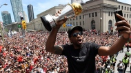 In this June 17, 2019, file photo, Toronto Raptors forward Kawhi Leonard takes a selfie holding his playoffs MVP trophy during the NBA basketball championship team's victory parade in Toronto. (Frank Gunn/The Canadian Press via AP, File)