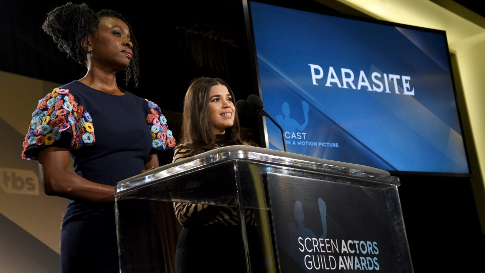 """Danai Gurira, left, and America Ferrera announce """"Parasite"""" as a nominee for outstanding performance by a cast in a motion picture at the 26th annual Screen Actors Guild Awards nominations announcement at the Pacific Design Center on Wednesday, Dec. 11, 2019, in West Hollywood, Calif. The show will be held on Sunday, Jan. 19, 2020, in Los Angeles. (AP Photo/Chris Pizzello)"""