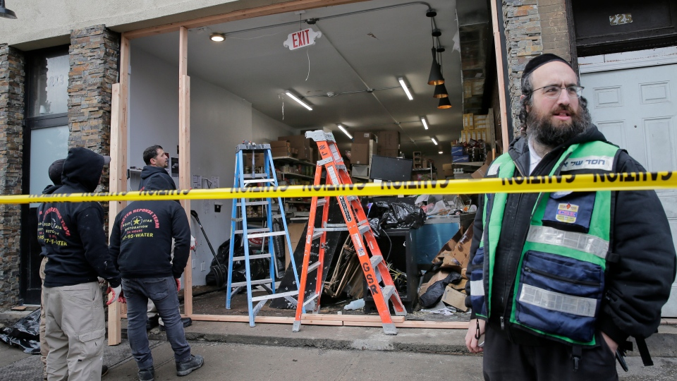 People work to secure the scene of a shooting at a kosher supermarket in Jersey City, N.J., on Wednesday, Dec. 11, 2019. Jersey City mayor Steven Fulop refused to call it an anti-Semitic attack but said surveillance video showed the gunmen driving slowly through the city's streets and then stopping outside a kosher grocery store, where they calmly got out of their van and immediately opened fire. (AP Photo/Seth Wenig)