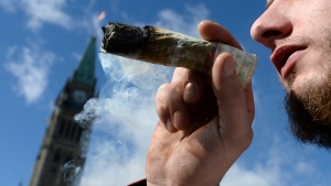A man smokes a marijuana joint during the annual 4/20 marijuana celebration on Parliament Hill in Ottawa on Friday, April 20, 2018. Statistics Canada says Canadians spent $908 million on non-medical cannabis since legalization and much of the population lives relatively close to a cannabis store. THE CANADIAN PRESS/Justin Tang