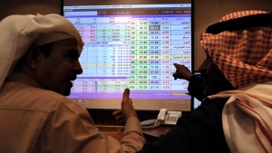 Saudi traders chat as they follow a screen displaying Saudi stock market values at the Arab National Bank in Riyadh, Saudi Arabia, Thursday, Dec. 12, 2019. Shares in Saudi Aramco gained on the second day of trading Thursday, propelling the oil and gas company to a more than $2 trillion valuation where it holds the title of the world's most valuable listed company. (AP Photo/Amr Nabil)