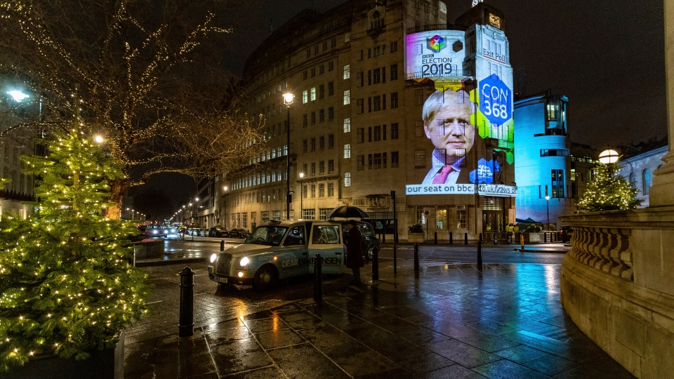 The results of an exit poll are projected onto the outside of Broadcasting House in London, just after voting closed for the 2019 General Election, Thursday, Dec. 12, 2019. An exit poll in Britain's election projects that Prime Minister Boris Johnson's Conservative Party likely will win a majority of seats in Parliament. That outcome would allow Johnson to fulfill his plan to take the U.K. out of the European Union next month. (AP Photo/Vudi Xhymshiti)