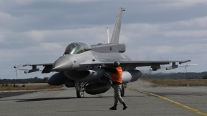 A Chilean air force F-16 fighter jet is directed on the tarmac as it arrives from searching for a missing C-130 Hercules transport plane, at the air base in Punta Arenas, Chile, Wednesday, Dec. 11, 2019. Searchers using planes, ships and satellites were combing the Drake Passage on Tuesday, hunting for the plane carrying 38 people that vanished en route to an Antartica base. (AP Photo/Fernando Llano)