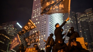 "A protestor holds a flag that reads: ""Liberate Hong Kong, Revolution of Our Times"" at a rally in Hong Kong, Thursday, Dec. 12, 2019. (AP Photo/Mark Schiefelbein)"