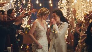 This image made from undated video provided by Zola shows a scene of its advertisement. Under pressure from a conservative advocacy group, The Hallmark Channel has pulled the ads for wedding-planning website Zola that featured same-sex couples, including two brides kissing. (Zola via AP)