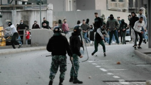 Supporters of the Shiite Hezbollah and Amal Movement groups, both supporting the current government, throw stones at riot policemen, as they try to attack anti-government protesters in downtown Beirut, Lebanon, Saturday, Dec. 14, 2019. The recent clashes marked some of the worst in the capital since demonstrations began two months ago. The rise in tensions comes as politicians have failed to agree on forming a new government. (AP Photo/Hussein Malla)