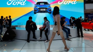 In this April 25, 2018, file photo, attendees visit the Ford booth during Auto China 2018 show held in Beijing, China. China's government says it will postpone planned punitive tariffs on U.S.-made automobiles and other goods following an interim trade deal with Washington. Sunday, Dec. 15, 2019's announcement came after Washington agreed to postpone a planned tariff hike on $160 billion of Chinese goods and to cut in half penalties that already were imposed. (AP Photo/Ng Han Guan, File)