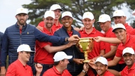 U.S. team player and captain Tiger Woods, center, holds the trophy with his players after the U.S. team won the President's Cup golf tournament at Royal Melbourne Golf Club in Melbourne, Sunday, Dec. 15, 2019. The U.S. team won the tournament 16-14. (AP Photo/Andy Brownbill)
